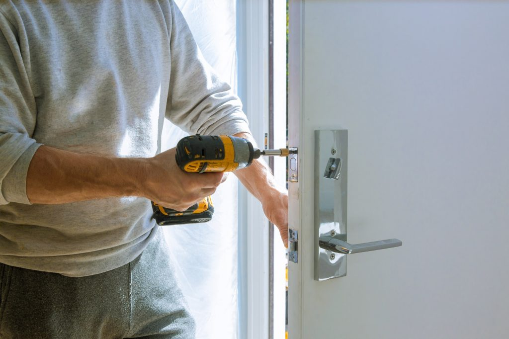 Cerrajeros Telde Installation with a lock in the door leaf using an drill screwdriver close-up.