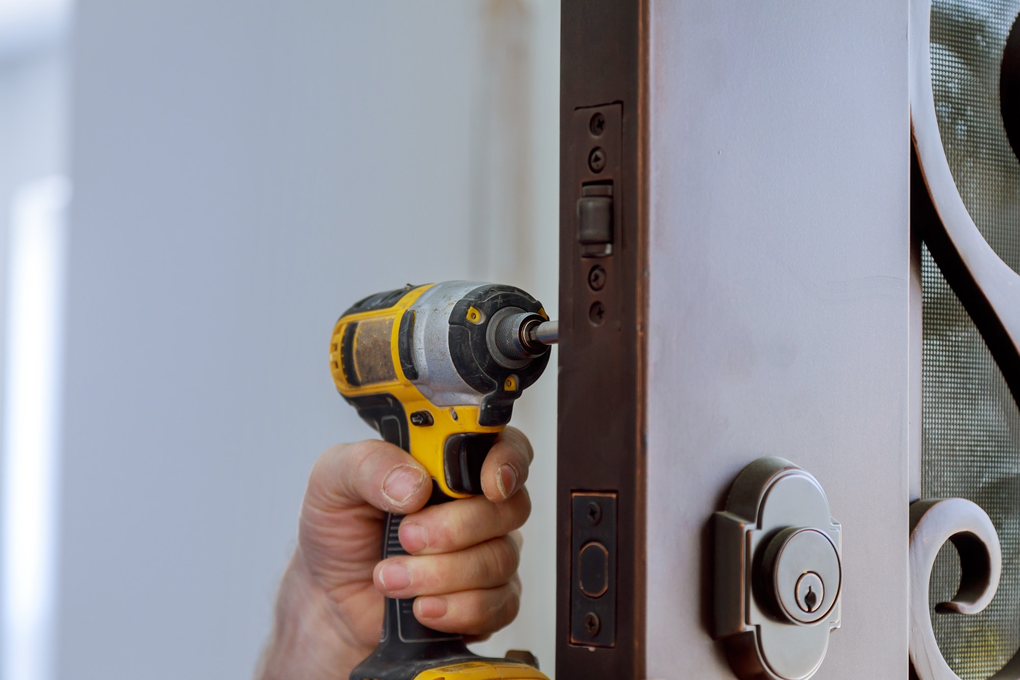 Cerrajeros zona Triana Locksmith hand holds the screwdriver in installing new house door lock