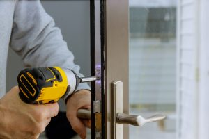 Cerrajeros Santa Lucia Locksmith in installing new house door lock hand holds the screwdriver